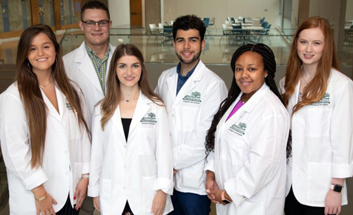 Multicultural group of six in white lab coats